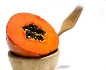 cutaneous: Half of freshly yellow orange papaya on wood bowl
