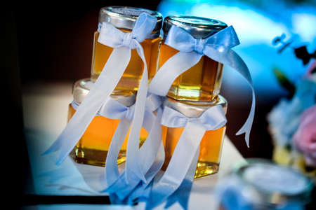 Honey jar with blue bow in the front wedding souvenir Stock Photo