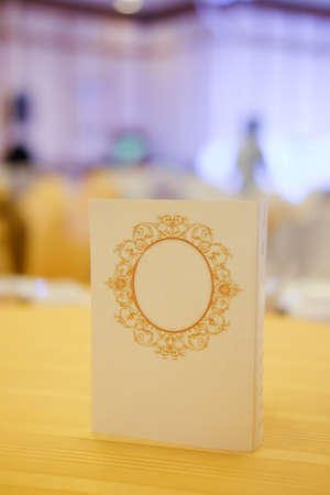 Close up of paper tent card on wooden table in wedding Stock Photo