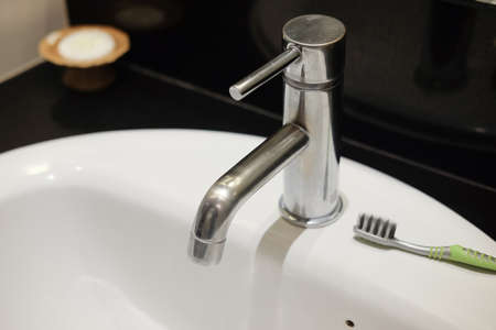 Water tap faucet in a white bathroom sink and toothbrush Stock Photo