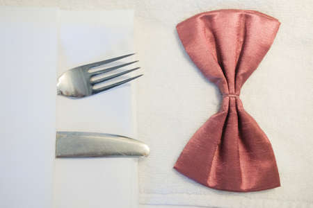 Close up of a bow tie lying on a table, dressing the groom. Morning before the wedding or a formal dinner.