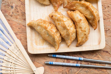 Japanese food Gyoza dumplings on wooden plate serve with chopsticks