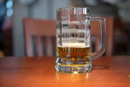 Almost empty glass mug of tasty craft beer in pub