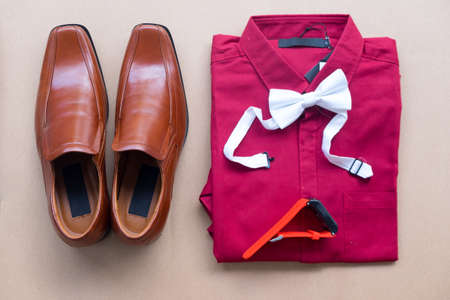 Flat lay of Groom accessories on brown background (brown shoes, red shirt, bow tie and smart watch)