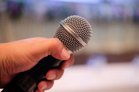 Close up of a man holding microphone - public speaking, conference, reportage Stock Photo