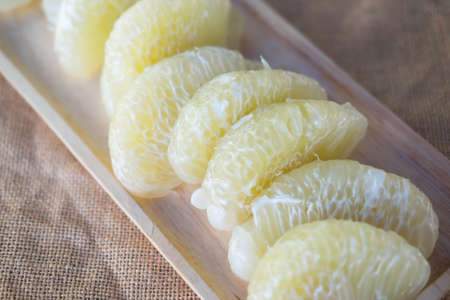 Close up of peeled pomelo fruit on wooden dish Archivio Fotografico