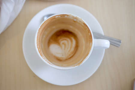 Empty coffee cup after drink on wood table.top view of coffee cup in coffee shop
