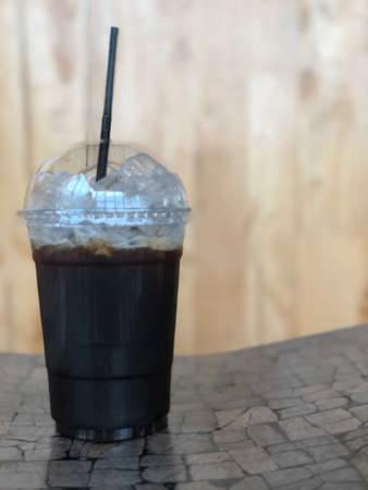 Iced black coffee or iced Americano with straw on wood table Stock Photo
