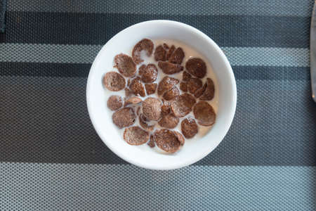 Chocolate corn flakes with milk in white bowl