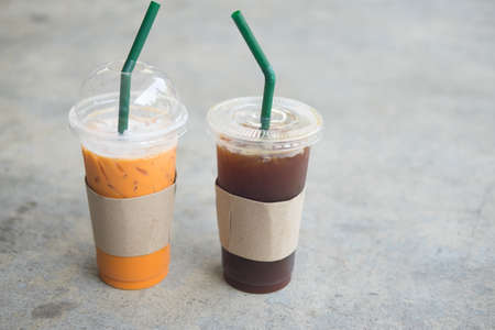 Close up iced Thai tea and iced black coffee in plastic cup