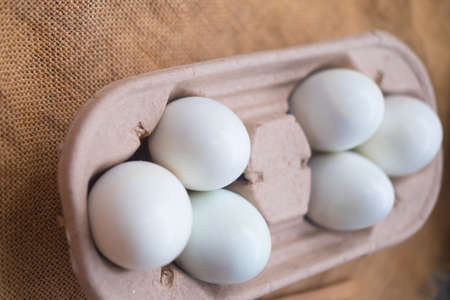 Fresh white raw eggs in shell eggs ready for cooking and diet food lie in an open cardboard container for carrying and storing eggs