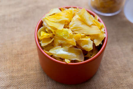 Close up of a pile of dried jackfruit chips in orange bowl Imagens