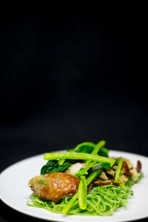 Roasted duck with green jade noodles on white dish