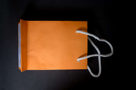 Mini orange paper bag with black background