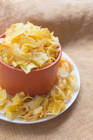 Pile of dried jackfruit chips served on orange bowl