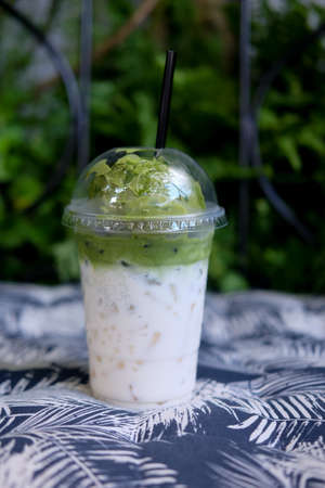 Ice cream green tea float on fresh milk in plastic glass in an outdoor natural setting Stock Photo