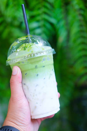 Ice milk green tea in plastic glass. Concept is easy beverage for traveler
