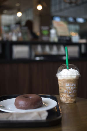 BANGKOK, THAILAND - JUNE 15, 2018: Starbucks coffee cold beverage and donut on table, famous coffee brand franchise originated in USA Redakční
