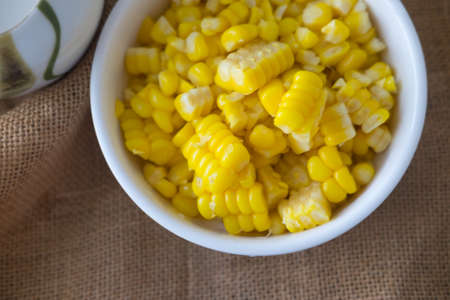 Baked corn seed in white bowl, top view Stock Photo