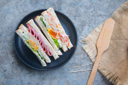 Sliced sandwiches cut with different filling - ham, salad, egg, bacon, whole grain bread Stock Photo