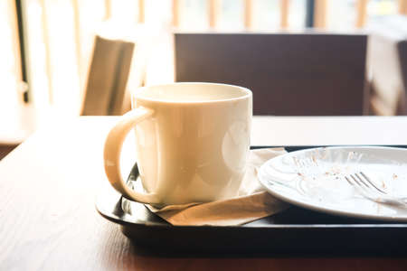 Empty coffee cup and empty plate after drink coffee and cake Stock Photo