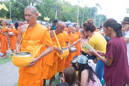 Saraburi, Thailand - July 29, 2018 : Group of monks receiving flower offering from people (Tak Bat Dok Mai or flower offering ceremony) at Phra Buddha Bat Woramahavihan Temple , Saraburi Province,Thailand