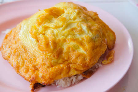 Omelette on top cooked rice on a pink plate