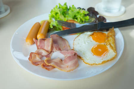 Delicious breakfast with fried eggs, hotdog and bacon Stock Photo