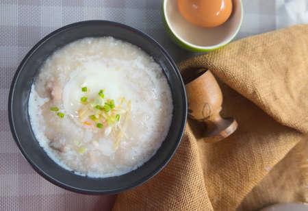 Rice porridge or congee with pork egg sliced ginger and vegetable.