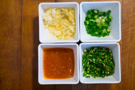 Set of shabu sauce on white bowl on wooden table Imagens