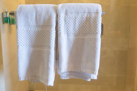 Clean white towels on a hanger at bathroom Stock Photo