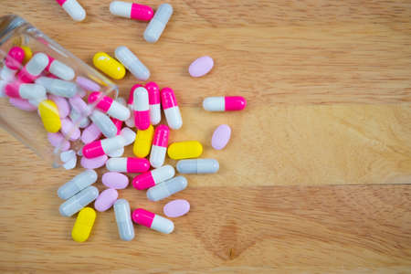 Many different colored pills on wooden background Stock Photo