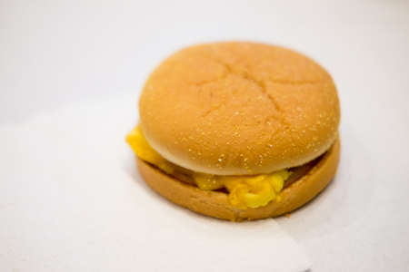 Homemade breakfast egg cheese muffin on white background