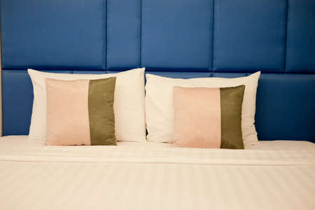 White down pillows leaning against blue wall