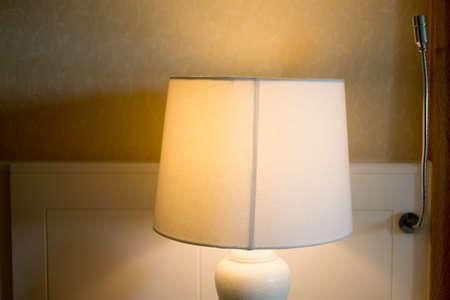 Bedside lamp on night in hotel bedroom Standard-Bild