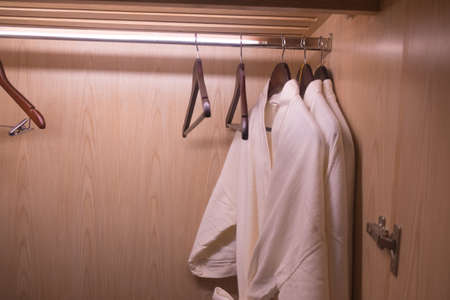 Close up of clothes hanger and bathrobe in wardrobe