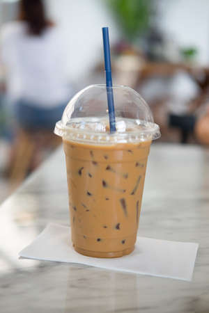 Iced mocha with blue straw in plastic cup