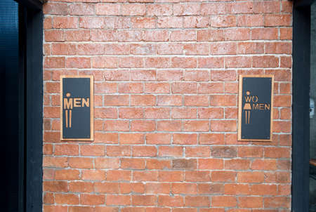 Front view of public restroom or toilet with man and women signs on brick wall decorate by vintage style in department store Standard-Bild