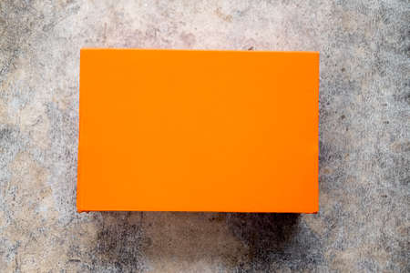 Orange shoe box with lid closed on cement background