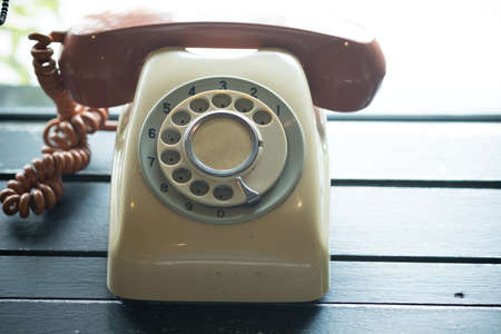 Old vintage telephone phone or landline on wooden retro desk. Old telephone concept Фото со стока