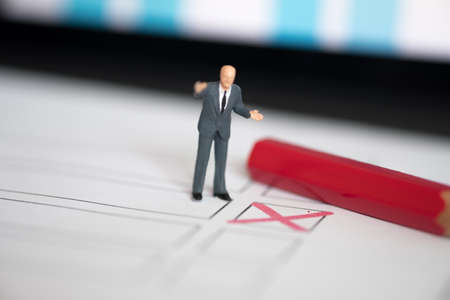Miniature people of a politician standing on election ballot with red pen. Election debates or press conference concept