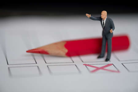 Miniature people of a politician standing on election ballot with red pencil. Election debates or press conference concept
