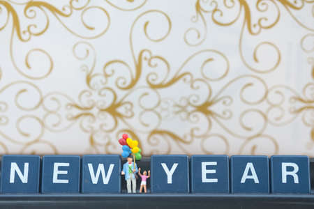 Miniature group happy family holding balloons with new year background. Selective focus Stock Photo