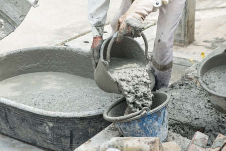 Worker pouring cement mix concrete in bucket at a construction site.
