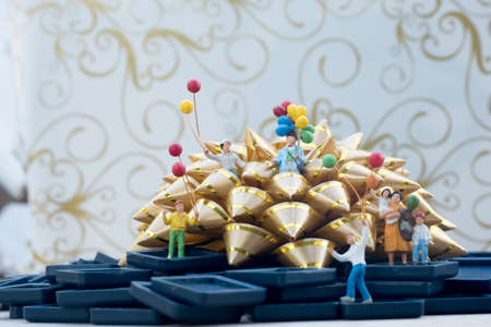 Miniature group happy family holding balloons standing on gold gift bow. Selective focus. Concept of happy family relations and carefree leisure time Foto de archivo