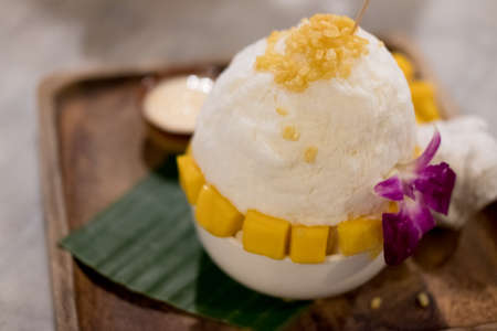 Mango Bingsu, shaved ice dessert with cubed sweet mango toppings. Bingsu Korea dessert