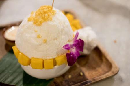 Bingsu mango served with sweetened condensed milk on table