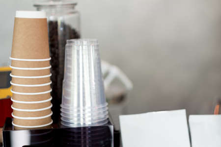 Rows of upside down transparent plastic cup and brown cardboard cups. As background coffee menu concept with copy space. Imagens