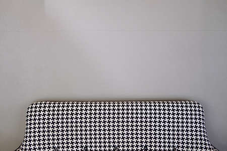 Black and white fabric sofa on cement wall in home