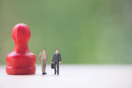 Miniature people: Two businessman standing with red pawn ready for business negotiations 写真素材